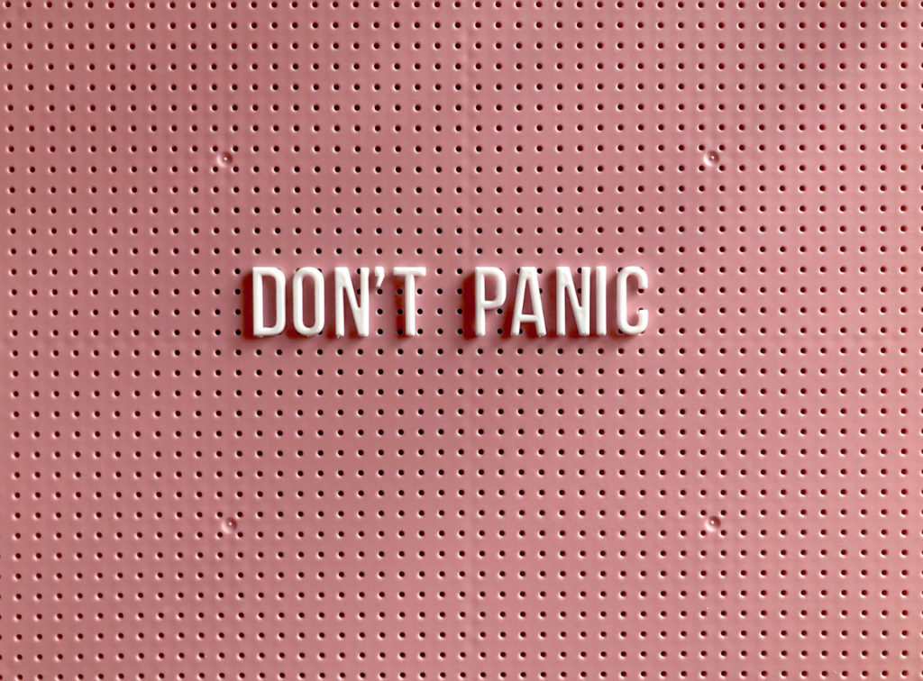 """A sign on a wall that reads """"don't panic."""""""