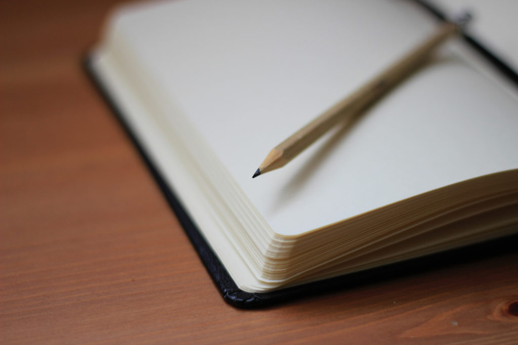 A pencil on an opened notebook.