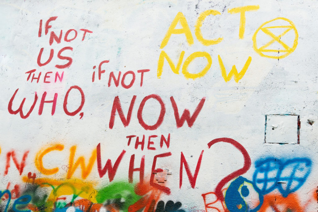 """A graffiti wall with the statement: """"If not us then who, if not now then when? Act now."""""""