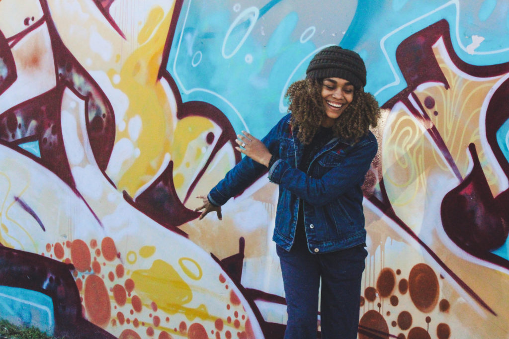 A woman smiling in front of graffiti.