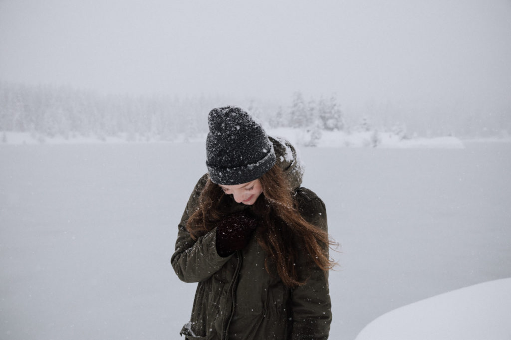A woman standing in a snowstorm, smiling.