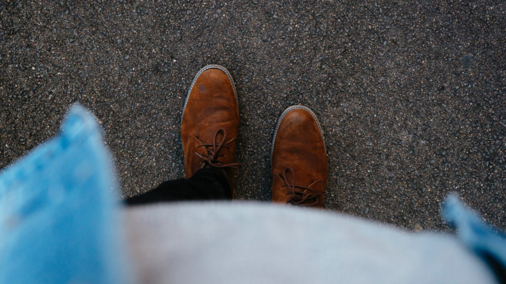 A person standing on a street, looking at their own feet.