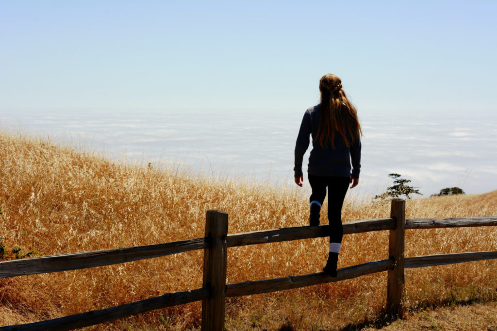 A woman stepping over a wooden fence in a field.
