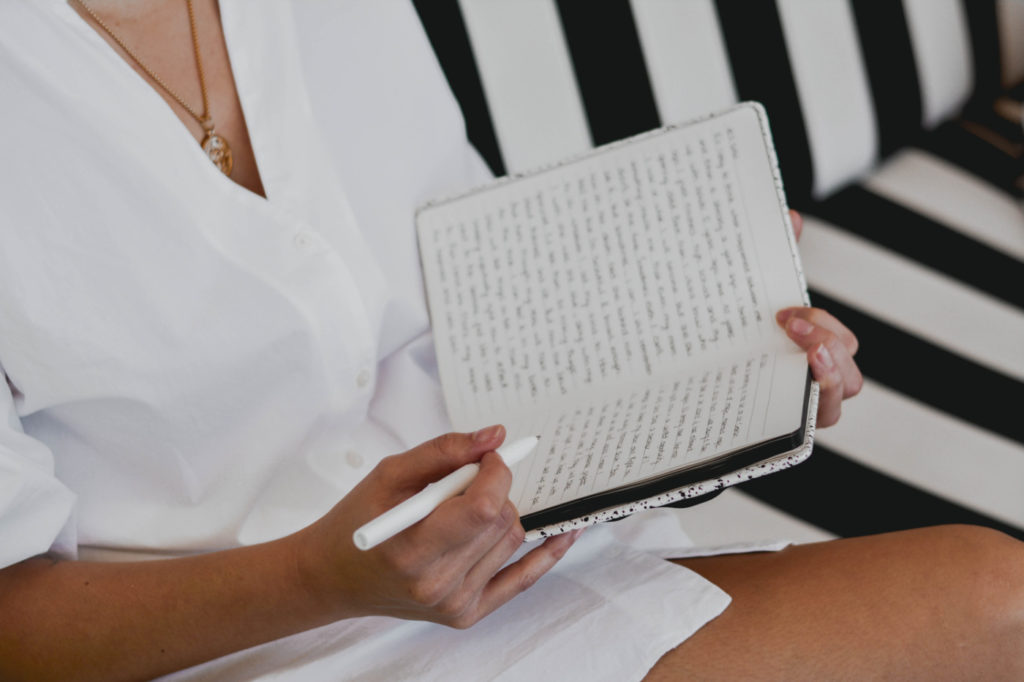 A person writing into a notebook.