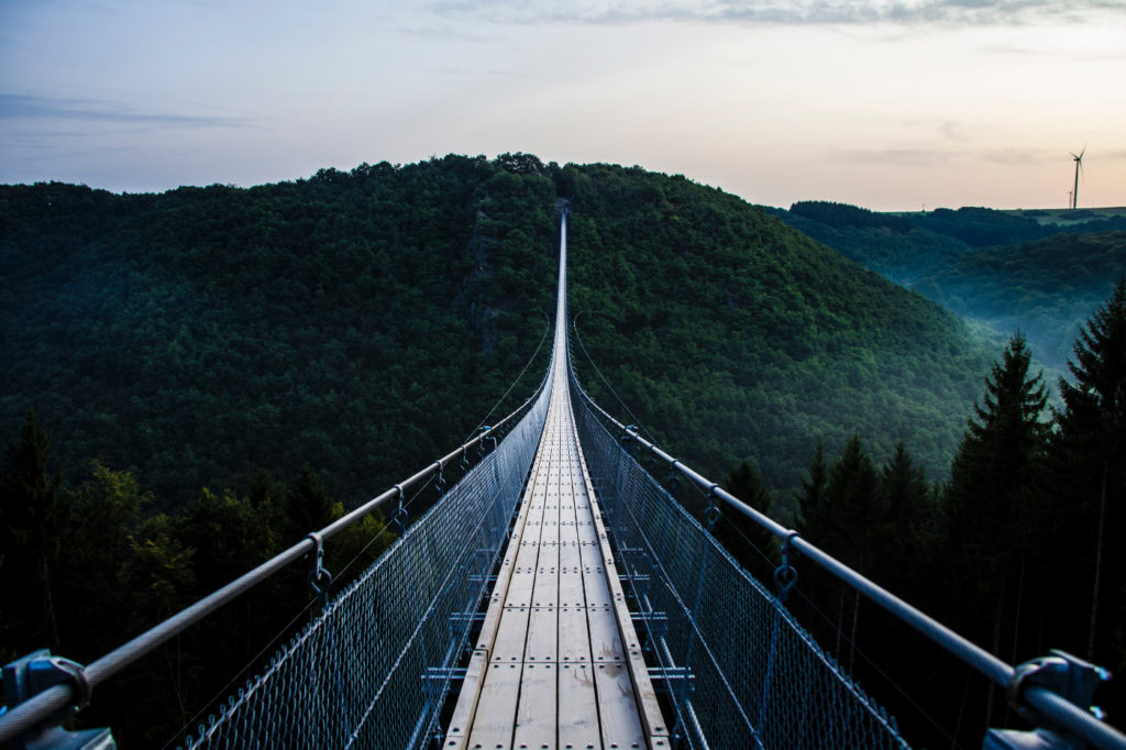An incredibly long hanging bridge across mountains covered by trees.