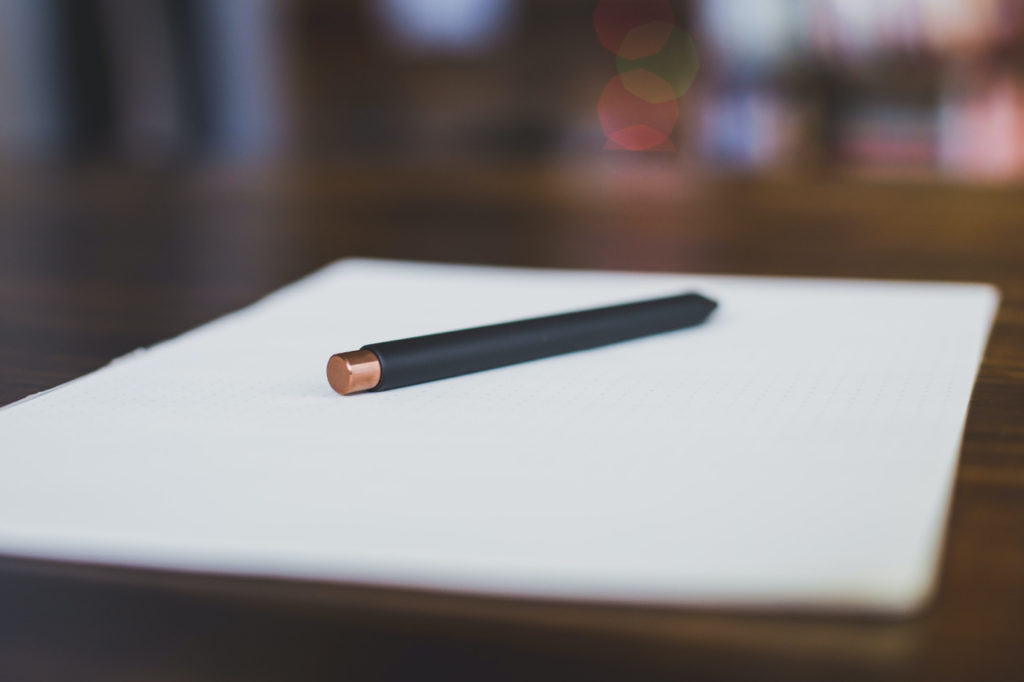 A pen on top of a blank piece of paper.