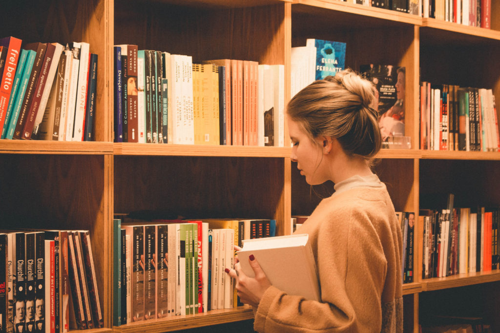 A person looking for a book in a library.