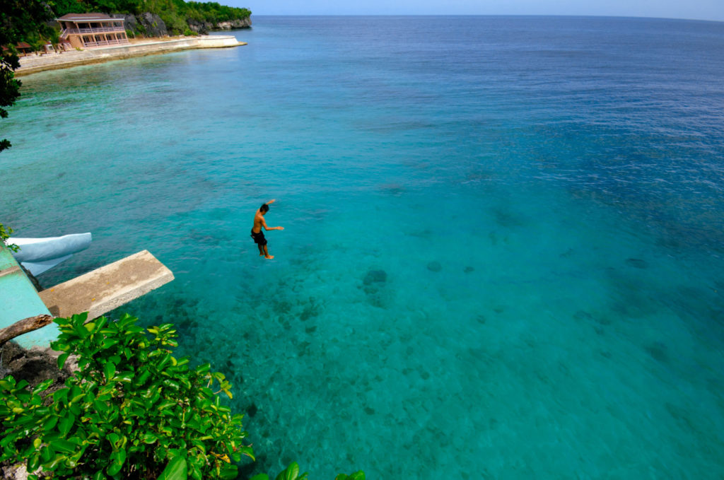 A person jumping into the ocean from a high diving board.