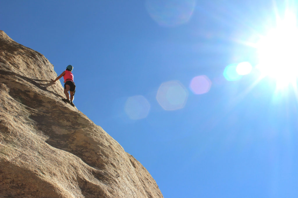 A person climbing on a steep cliff.