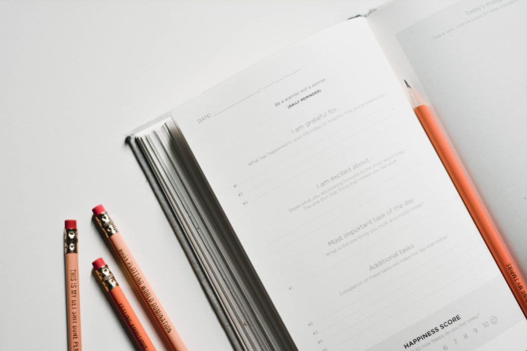 A journal on a desk next to several pencils.