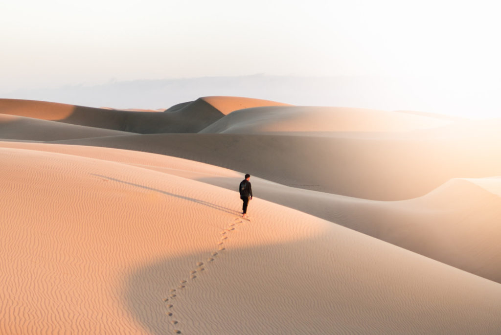 A person walking on a dune in a desert.