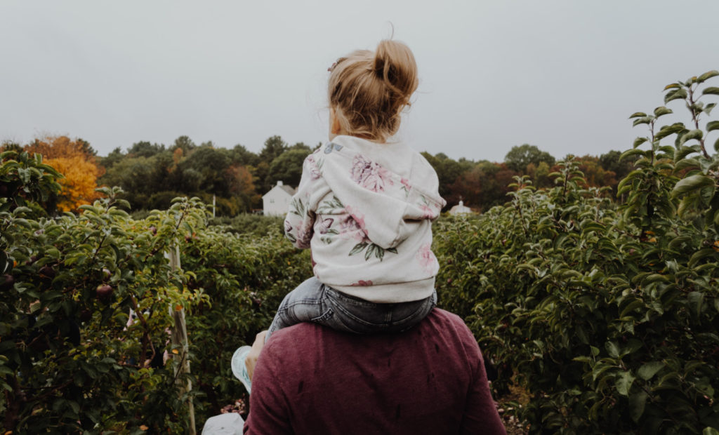 A person carrying a child on their shoulders.