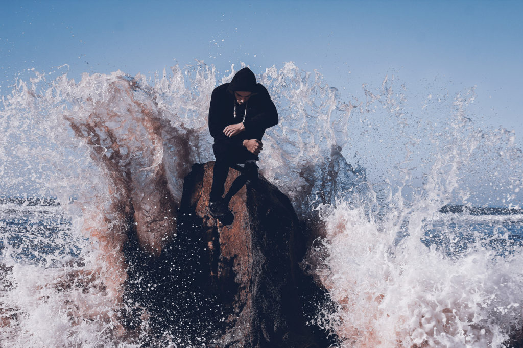 A large wave hitting a man sitting on a rock formation at sea.