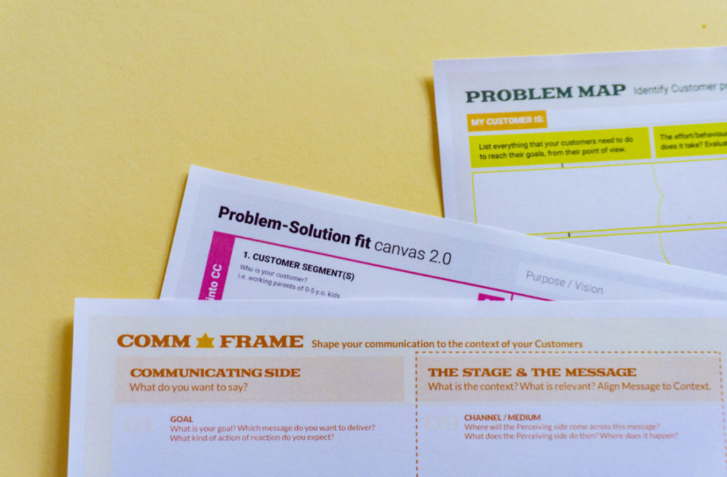 """A stack of papers on a desk with a prominent one showing """"problem-solution fit canvas"""" text"""