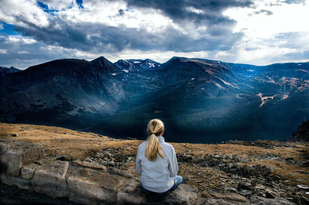 A person in contemplation looking at distant mountains.