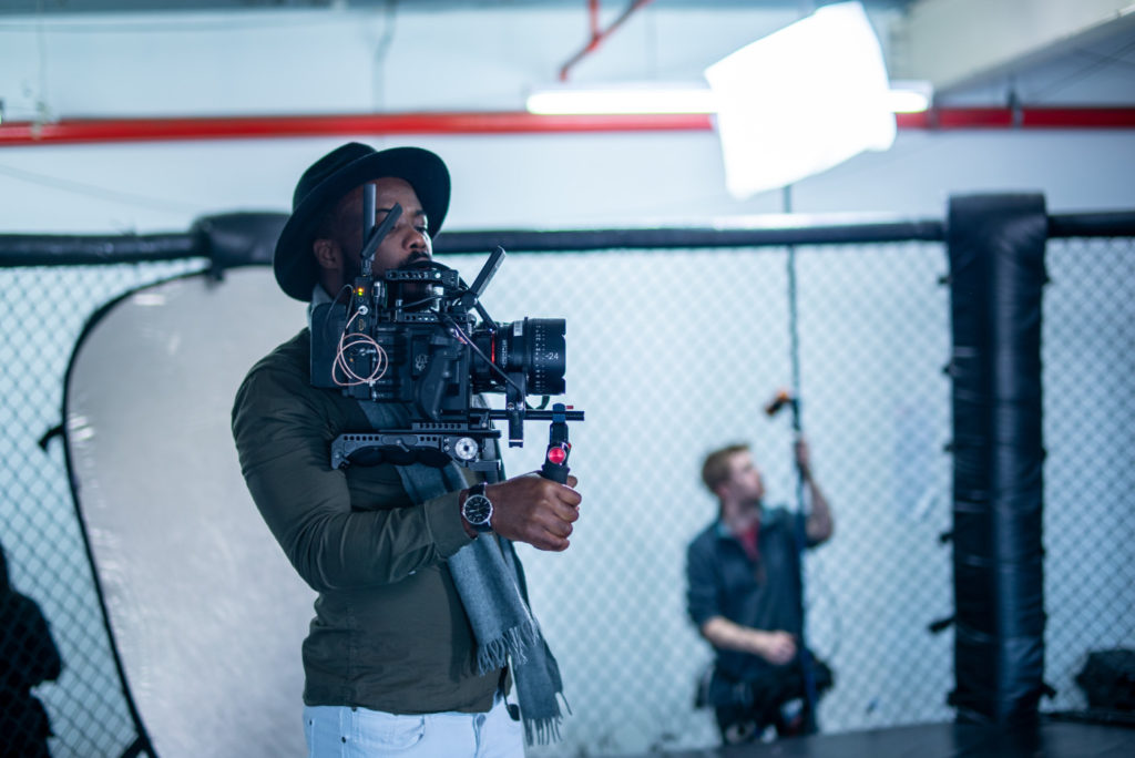 A cameraman on a film set holding a large camera.