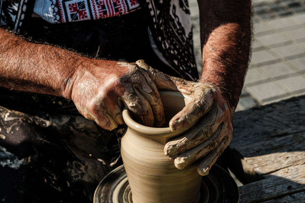A person molding a clay pot on a wooden table.