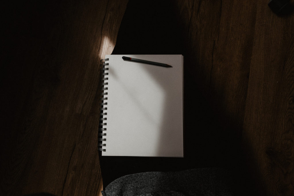 A pen and an empty notebook on a desk.
