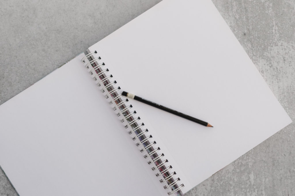 A pencil and an empty open notebook on a desk.