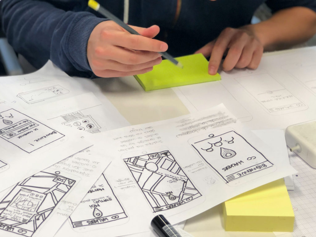 A person writing on a sticky note on a desk full of diagrams and plans.