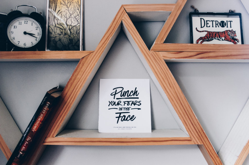 """""""Punch your fears in the face"""" poster on a wall shelf."""