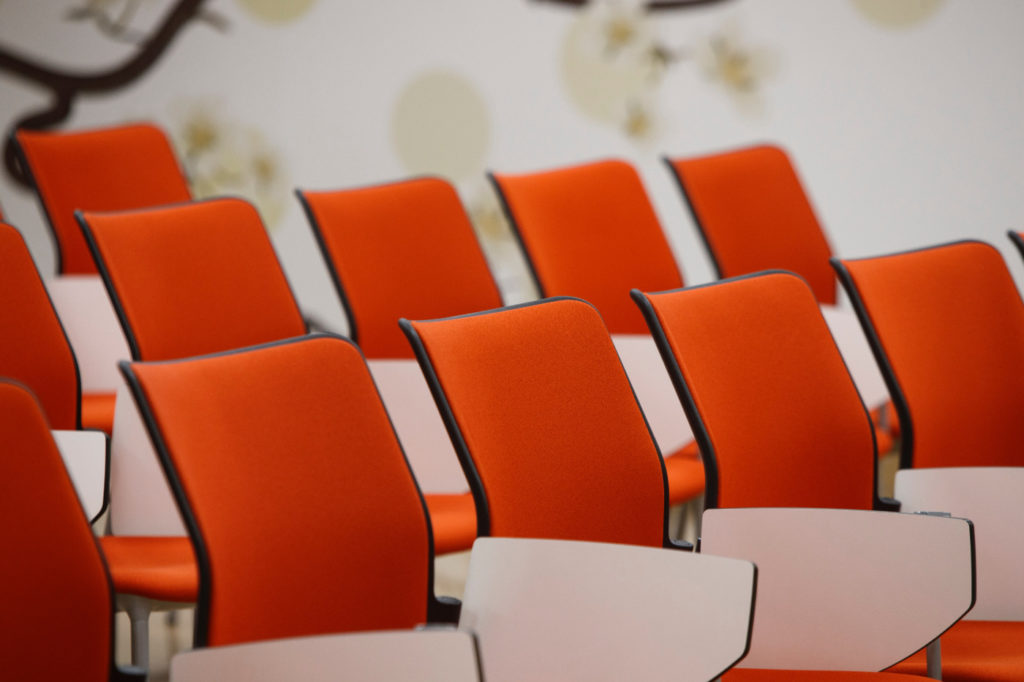 A row of empty seats in a conference room.