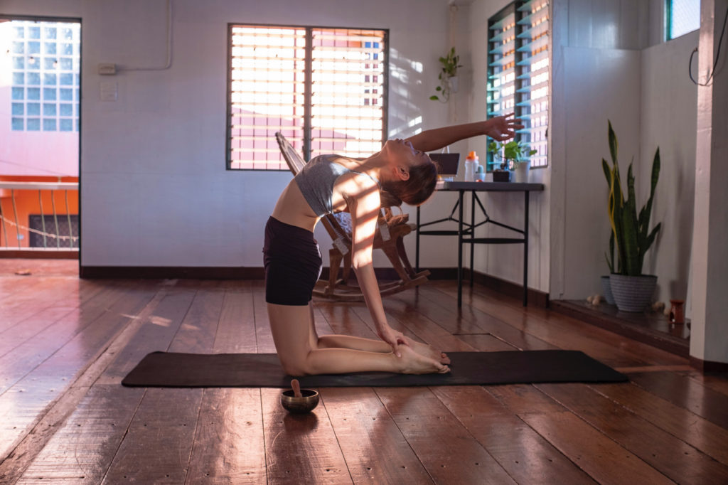 A woman practicing yoga in a home office.