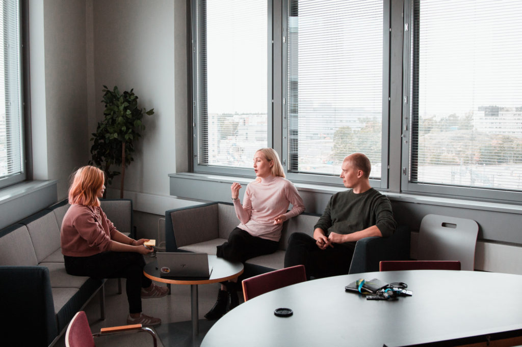 Three people in a discussion at a desk.