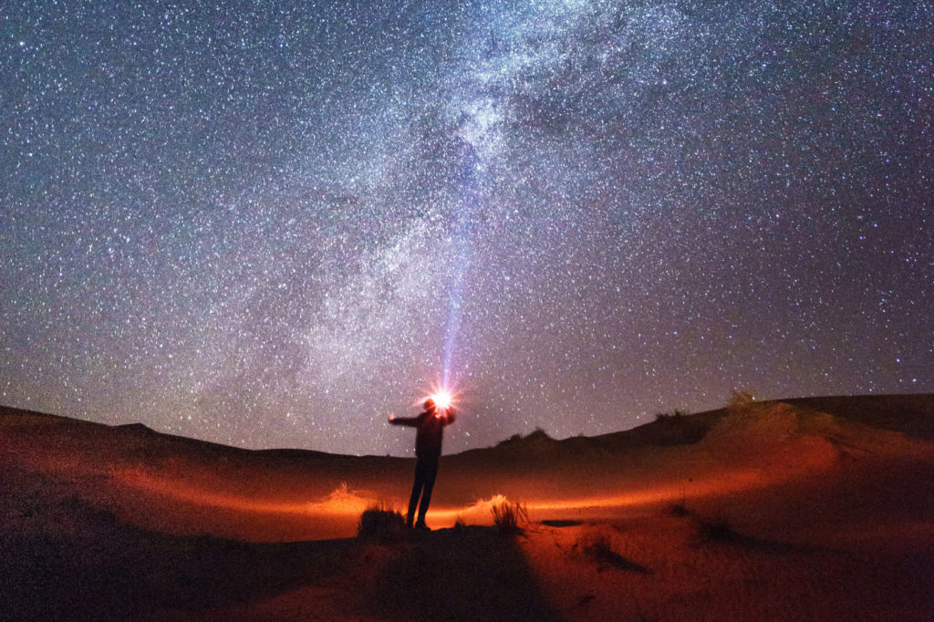 A person holding a bright light underneath a starry sky.