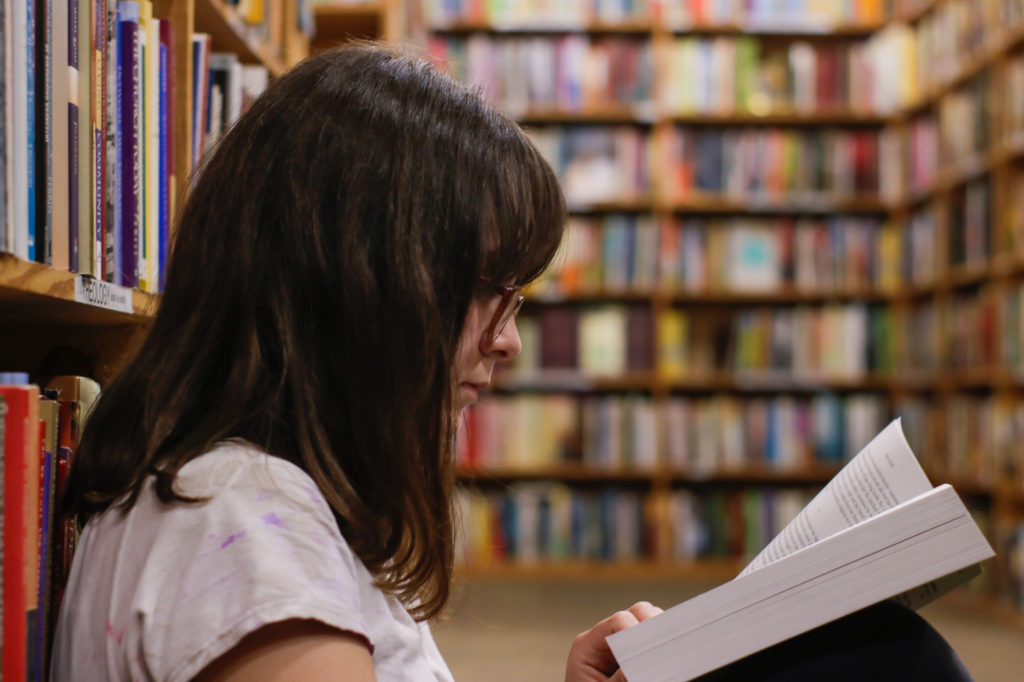 A person reading a book in a library.